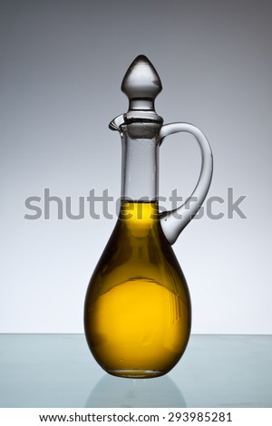 Olive oil bottle in back light. - stock photo