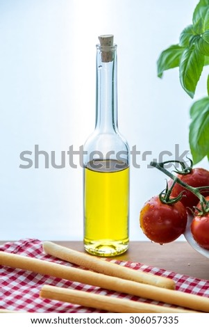 Olive oil bottle with tomatoes, basil and bread-sticks - stock photo