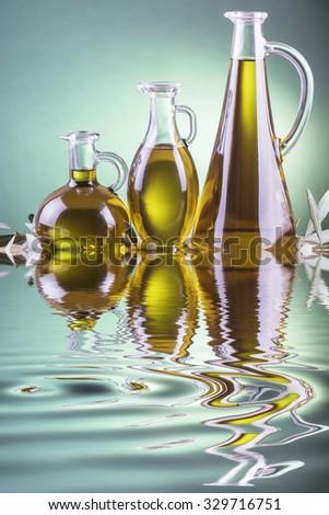 Olive oil bottles on a green spotlight background - stock photo