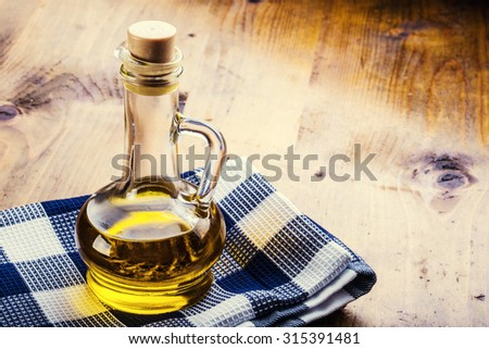 Olive oil. Carafe - Bottles of olive oil blue checkered cloth on a wooden table - stock photo