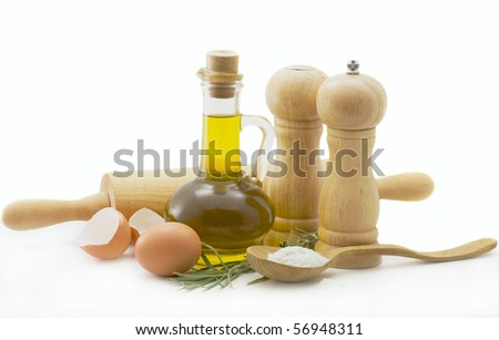 Olive oil, eggs, spices and a wooden spoon on a white background - stock photo