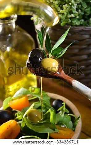 Olive oil falling on two olive with olive leaves to flavor a Mediterranean salad .Typical dish of the Mediterranean diet - stock photo