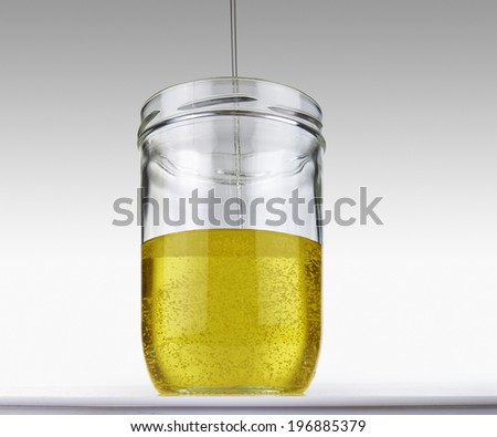 Olive oil flowing into glass jar on a grey gradient background - stock photo