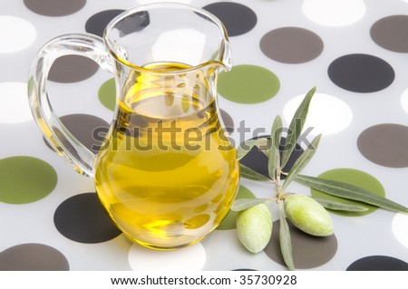 Olive oil in a small jug and some olives on colourful background
