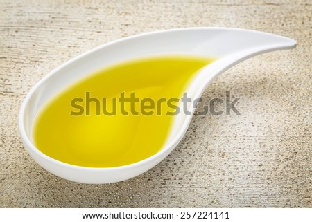 olive oil in a teardrop shaped bowl against white painted grunge wood - stock photo