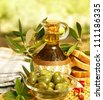 Olive oil in bottle and fresh green olives in glass plate on the table, healthy organic nutrition, traditional Lebanese cuisine, ripe fruits, food still life, Mediterranean vegetables, autumn season - stock photo