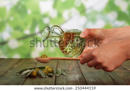 Olive oil in bottle and olives in hands - stock photo