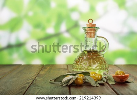 Olive oil in bottle and olives on table - stock photo