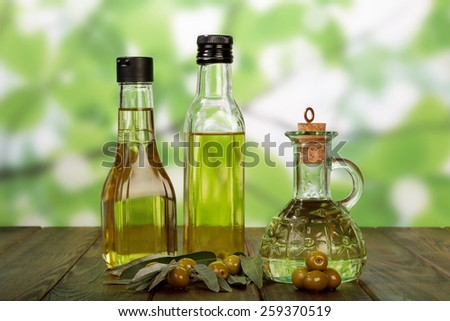 Olive oil in bottles and olives on table - stock photo
