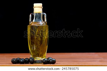 Olive oil in the bottle on the wooden table - stock photo