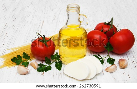 olive oil, mozzarella cheese, spaghetti, garlic and tomatoes on a old wooden background