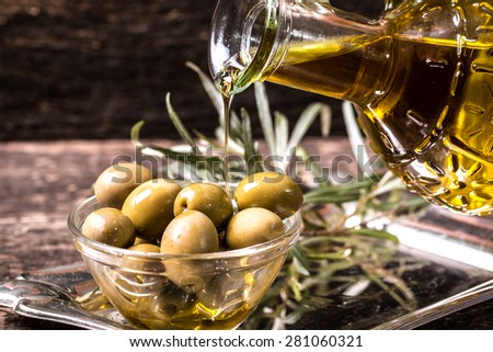 Olive oil on wooden table - stock photo