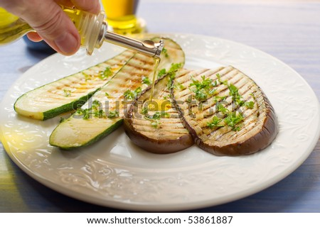 olive oil over grilled  zucchinis and eggplant on dish - stock photo
