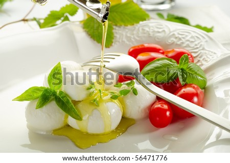 olive oil over mozzarella and tomatoes