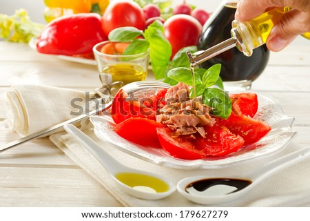 olive oil over salad with tuna and tomatoes - stock photo