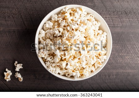 Olive oil popped popcorn in a porcelain bowl top view on a dark wooden background - stock photo