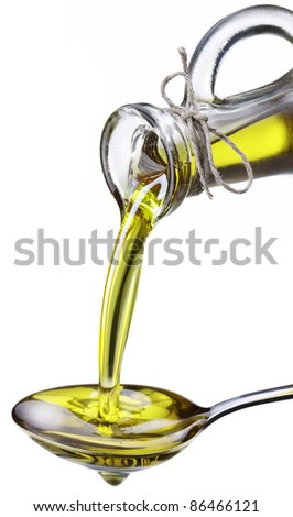Olive oil poured from a bottle on a metal spoon. Image isolated on a white background. - stock photo