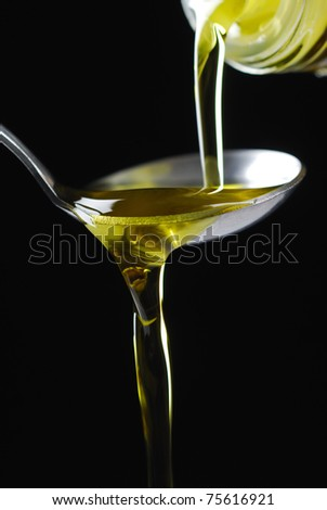 olive oil poured from bottle - stock photo