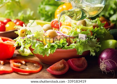 olive oil pouring into bowl of fresh vegetable salad - stock photo