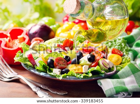 olive oil pouring into plate of fresh greek salad - stock photo