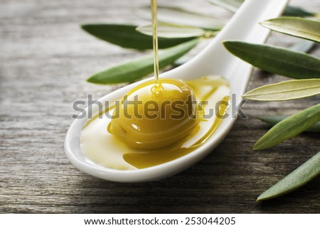 Olive oil pouring on the spoon close up