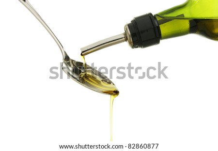 Olive oil pouring onto a spoon from a green bottle against a white background - stock photo