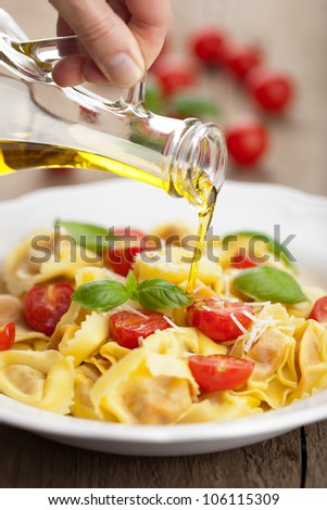 olive oil pouring over tortellini with cheese and tomatoes - stock photo