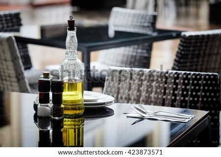 Olive oil, salt and pepper on a table for dining