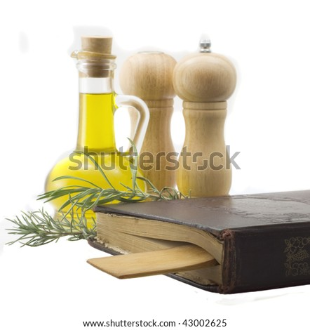 Olive oil, spices and a old recipe-book and wooden spoon on white background - stock photo