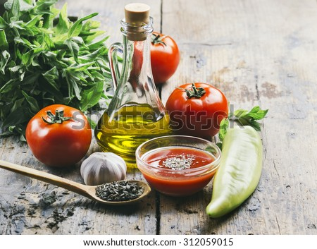 Olive oil, tomato and herbs on rustic wooden table - stock photo