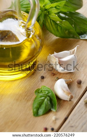 Olive oil with basil leaves and garlic on wooden table