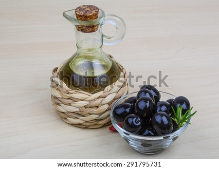Olive oil with berries on the wood background - stock photo