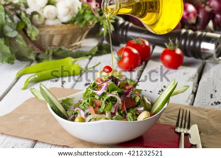 olive oil with bowl of salad - stock photo