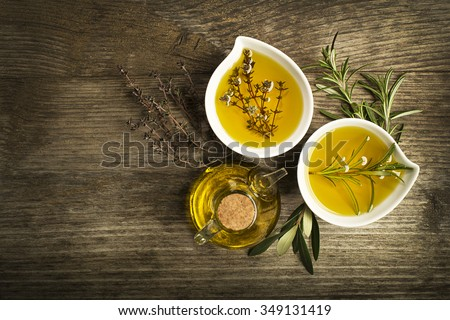 Olive oil with fresh herbs on wooden background. - stock photo