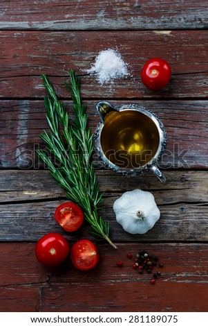Olive oil with herbs and spices selection on rustic wooden background. Cooking, vegetarian food or health concept. - stock photo