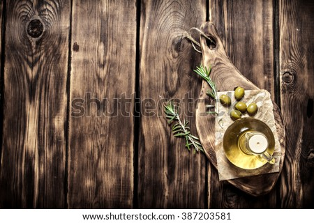 Olive oil with rosemary branch. On a wooden background. - stock photo