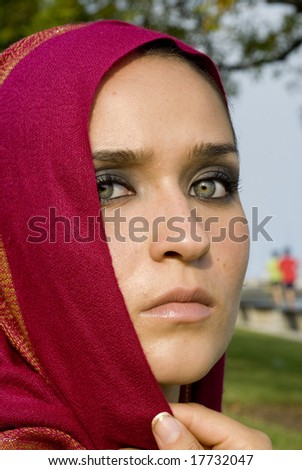 Olive skinned female with fuchsia headscarf looking at the camera - stock photo