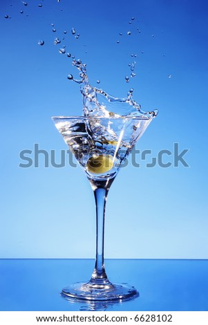 Olive splashing in a Martini glass - stock photo