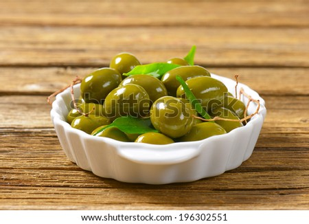 olive tapas in the ceramic tray, decorated with twigs and leaves - stock photo