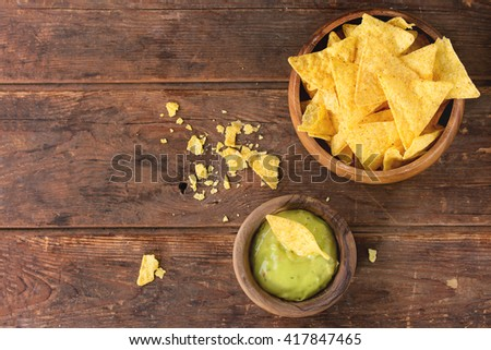 Olive wood bowl of mexican nachos chips with guacomole sauce over old wooden background. Top view. With space for text - stock photo