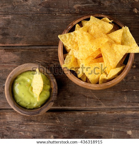 Olive wood bowl of mexican nachos chips with guacomole sauce over old wooden background. Top view. Square image
