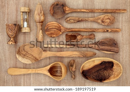 Olive wood kitchen utensil selection over papyrus background. - stock photo