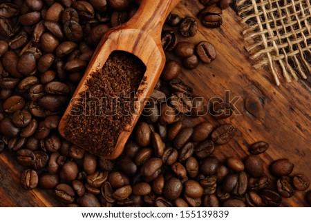 Olive wood measuring scoop with coffee beans, ground coffee and burlap on rustic dark wood background.  Low key still life with directional, natural lighting. - stock photo