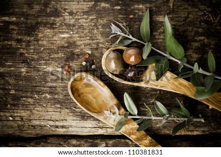 Olive wood spoons with fresh olives and leaves on an old grungy textured wooden tabletop with copyspace - stock photo