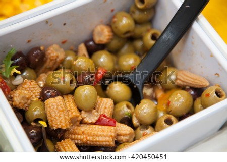 Olives and baby corn in a bowl in a self service salad bar in a hotel canteen - stock photo