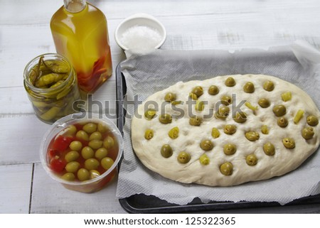 olives and olive oil focaccia dough. The focaccia its a traditional italian bread made with flour and olive oil. Traditionally its topped with olives. This is the dough before baked - stock photo