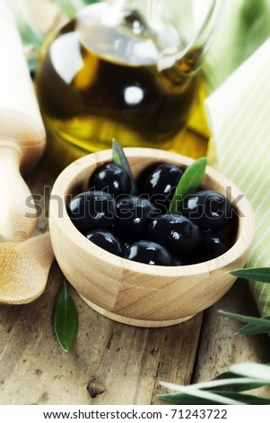 Olives and Olive Oil on old tablel - stock photo