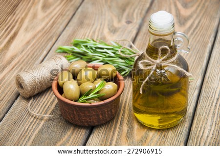 Olives and Olive Oil on wooden table - stock photo