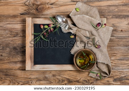 olives and olive oil with menu board - rustic setting  over a rustic wooden background  - stock photo