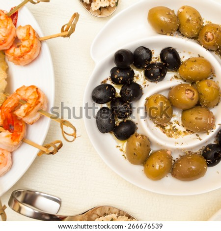 Olives and prawns on a tapas table - stock photo